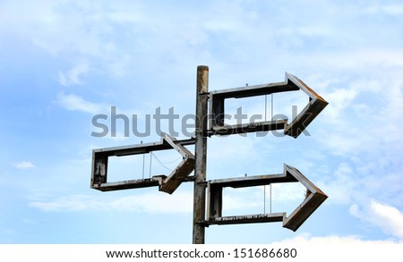 "Three metal arrows point in the same direction.  Blue sky backs old sign with only the metal remaining.  Metaphor for ""point of no return"", ""point the way"", ""point me in the direction"" - stock photo"