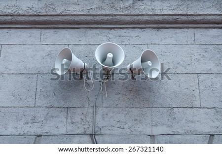 Three metal loudspeakers on building - stock photo