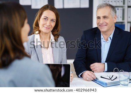 Three middle-aged stylish business executives in a meeting in the office sitting around a table having a discussion
