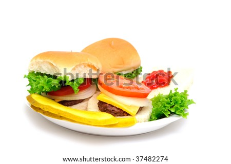 Three mini-burgers topped with cheddar cheese, white onion, tomato and lettuce on a white plate with sliced dill pickles on the side isolate on a white background - stock photo