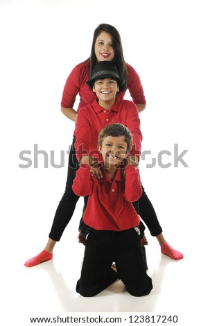 Three mixed race (Asian Indian and caucasian) siblings dressed in red and black, arranged totem-pole style.  On a white background. - stock photo