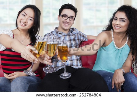 Three mixed race people sitting on sofa while toast with champagne and smiling at the camera