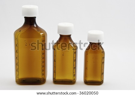Three mixed size brown medicine bottles on a white background. - stock photo