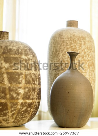 Three modern brown vases in front of gauzy curtains.