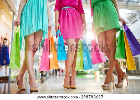 Three modern girls in bright dresses and stylish shoes holding paperbags