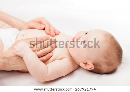 Three month baby girl is receiving abdominal massage from a female massage therapist - stock photo