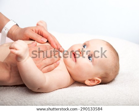 Three month baby girl is receiving chest massage from a female massage therapist - stock photo