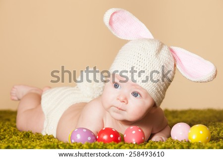 Three months baby lying on his stomach as a Easter bunny on the grass with eggs - stock photo