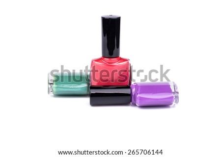 Three multi-colored nail polish, red, turquoise and purple on a white background