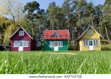 three multi-colored small tiny house on the lawn in the forest - stock photo