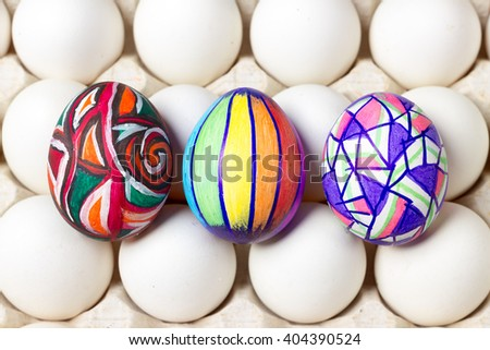 three multicolored painted easter eggs lying on white tray, holiday celebration food photography
