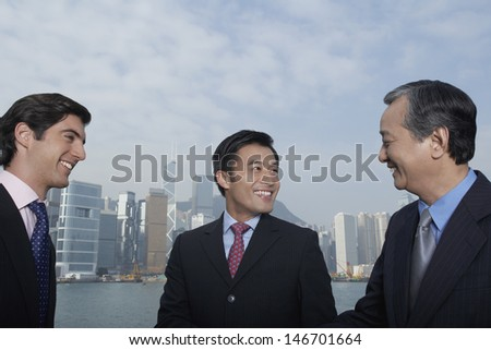 Three multiethnic business people discussing with city skyline in background - stock photo