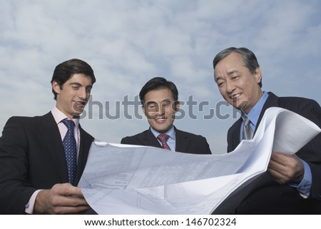 Three multiethnic business people looking at blueprint against cloudy sky - stock photo