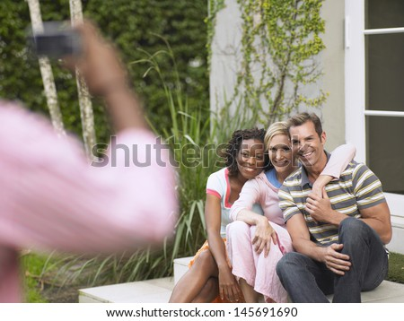 Three multiethnic friends being photographed outdoors