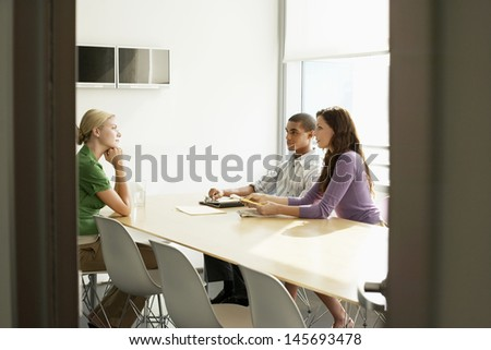 Three multiethnic office workers in conference room