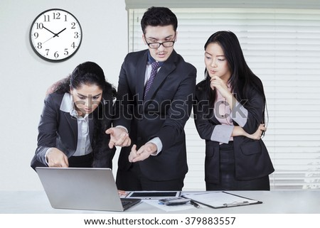 Three multiracial workers meeting in the office and using laptop to discuss and make business plan