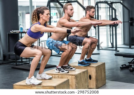 Three muscular athletes doing jumping squats on a wooden box - stock photo