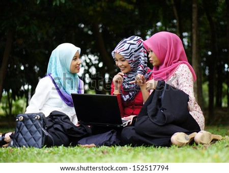 Three muslim girl with notebook at park - stock photo