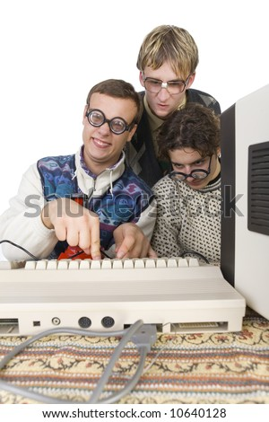 Three nerdy guys sitting in front of old-fashioned computer. One of them is pushing the button on keyboard and looking at camera. front view, white background - stock photo