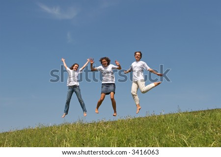 Three nice girls jump on a green grass on a background of the blue sky