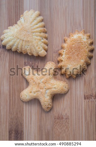 Three Norwegian christmas shortbread cookies on a wooden bamboo cutting board