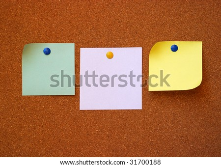 three note pads on cork board