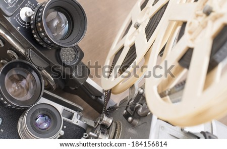 Three objects Vintage old movie and photo camera with lens a reel of film Projector - stock photo
