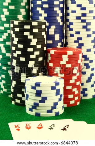 Three of a king hand in front of several piles of poker chips on a green table