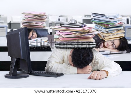 Three of businesspeople sleeping on the table with a pile of paperwork on their head, shot in the office