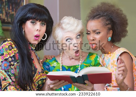 Three offended mature women reading a hardcover book - stock photo
