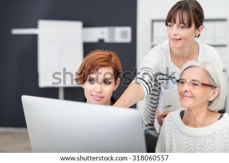 Three Office Women Looking at Computer Screen Together Inside the Workplace.