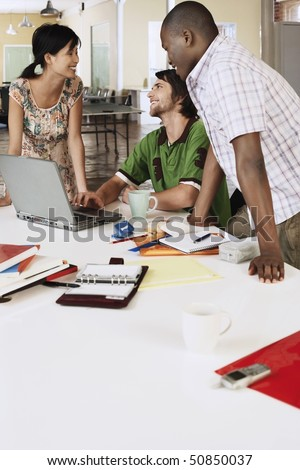 Three office workers around laptop, smiling. - stock photo