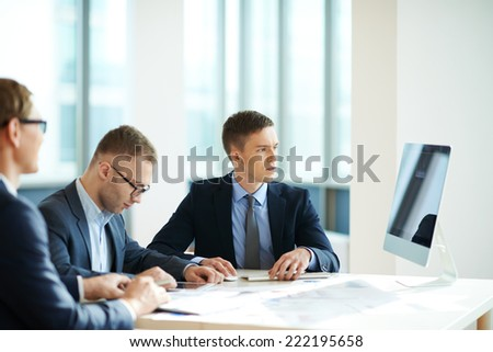 Three office workers having meeting - stock photo
