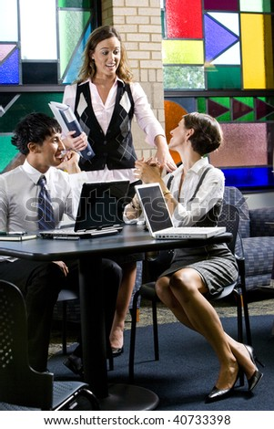 Three office workers meeting and conversing in colorful boardroom - stock photo