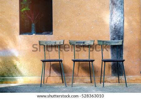 Three old chairs against a wall