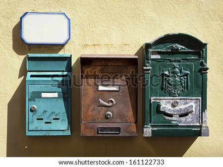three old letterboxes and a nameplate