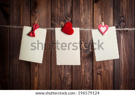 three old paper sheet with bow and hearts hanging on clothesline against wooden background - stock photo