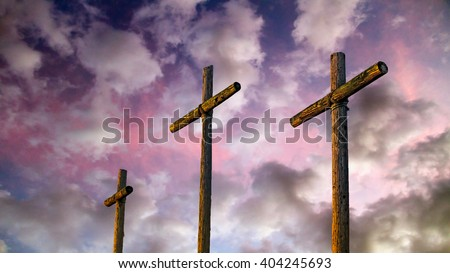 Three old rugged wooden crosses stand tall against an amazing and dramatic sky at sunset.