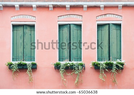 three old windows with shutters and small flowerpots