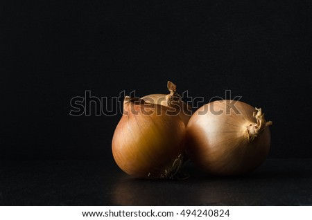 Three onions grouped in still life composition on slate surface with black chalkboard background and copy space.