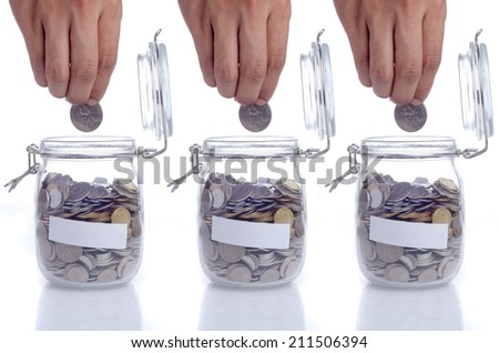 Three open glass jar with coin, hand putting the coin and empty space for text  - stock photo