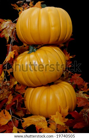 Three orange autumn pumpkins stacked ontop of each other on a black background with some leaves.