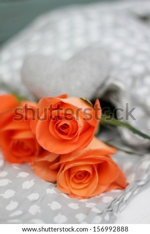 Three orange roses with grey tweed shabby chic heart, on grey and white cotton fabric, a romantic image, wedding or valentines day , shallow depth of field