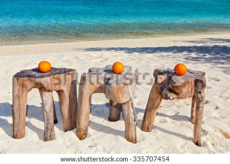Three oranges are on original  beach tables are made from trunk of tree - stock photo