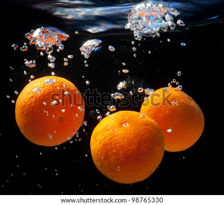 three oranges in water with bubbles. On a black background - stock photo