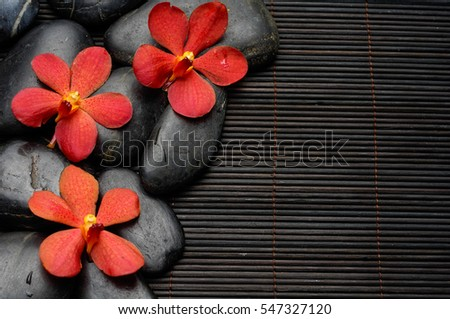 Three orchid and stones on mat background