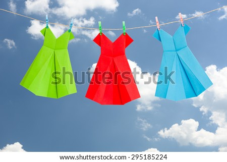 Three Origami paper dresses (green, red, blue) hanging on a clothes line in front of the blue summer sky with clouds. - stock photo