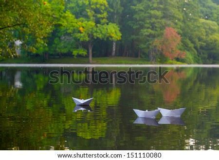 Three origami paper ship floating on the river - stock photo