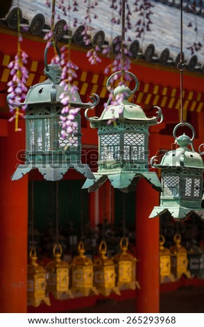 Three ornate metal lanterns hanging at a Japanese temple. Shallow depth of field with selective focus on the middle lantern. - stock photo
