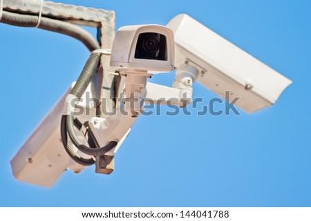 Three outdoor video surveillance camera on the bracket. - stock photo